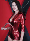 Beautiful brunette in shiny red outfit with whip